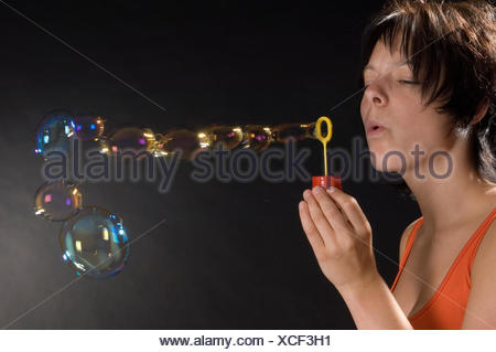young girl blowing bubbles - Stock Photo
