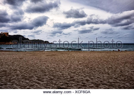 Scenic View Of Beach Against Cloudy Sky - Stock Photo