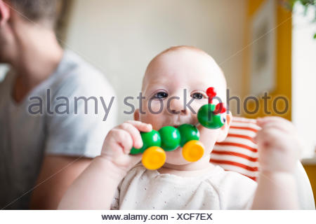Portrait of cute baby girl biting toy with father in background at home - Stock Photo
