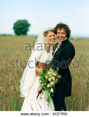 Scandinavia, Sweden, Oland, Bride and groom standing in field, smiling, portrait - Stock Photo