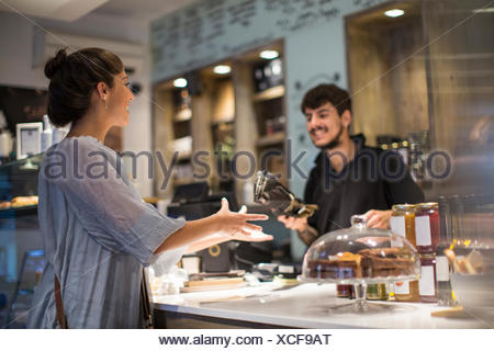 Barista handing baguette to female customer at cafe counter - Stock Photo