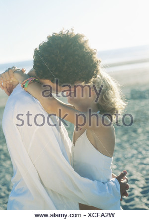 Teenage couple kissing on beach - Stock Photo