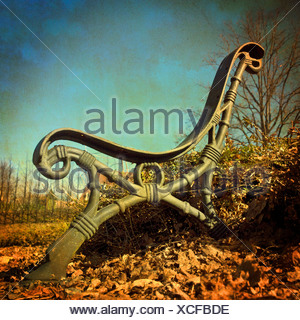 Cast iron seat outdoors in park in autumn - Stock Photo