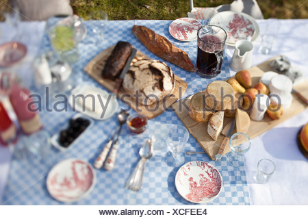 cheese wheels, bread and a lot of crockery on a dining table outside - Stock Photo
