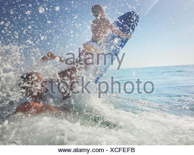 Father and son playing in ocean with surfboard - Stock Photo