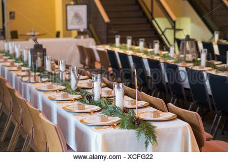 Wedding reception tables with seating, plates, and candles at a winter wedding in Oregon. - Stock Photo