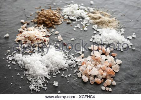 Different types of salt crystals, sea salt, himalaya coarse salt, fleur de sel, chipotle flingsalt, hickory smoked salt, stone salt and garlic salt - Stock Photo