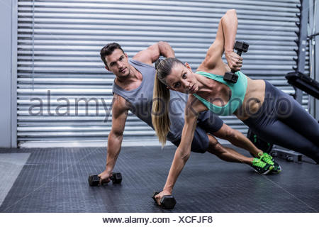 Smiling muscular couple doing side plank - Stock Photo