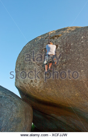 Young man climbing with ropes on boulder - Stock Photo