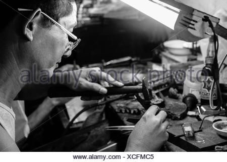 Mid Adult Man Using Hammer In Workshop - Stock Photo
