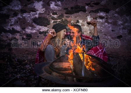 Romantic mature couple wrapped in blanket in front of campfire at night - Stock Photo