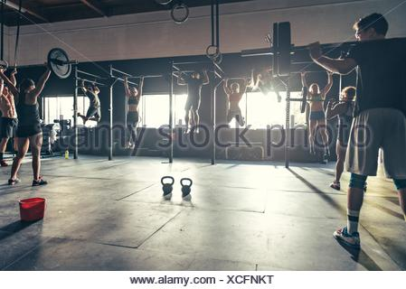 Team training using varied equipment in gym - Stock Photo