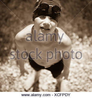 Portrait of a boy standing on beach wearing swimming trunks, swimming cap and goggles - Stock Photo