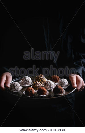Variety of homemade dark chocolate truffles with cocoa powder, coconut, walnuts on vintage tray in kid's hands in black shirt. Dark background. - Stock Photo