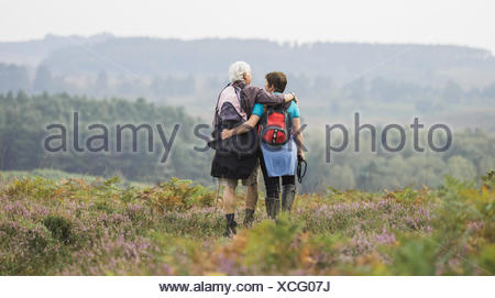 A couple standing on a path looking at the view over wooded hills, with arms around each other. - Stock Photo