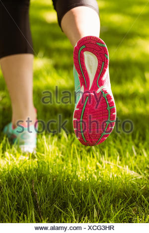 Woman in running shoes jogging on grass - Stock Photo