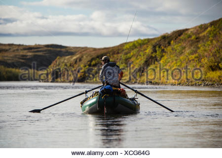 A man scans the water for salmon while rowing his raft down an unnamed creek in western Alaska. - Stock Photo