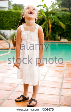 Young Hispanic girl standing and laughing by a pool - Stock Photo