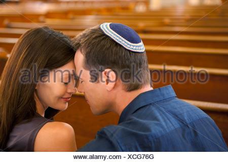 Man in yarmulke praying with girlfriend - Stock Photo