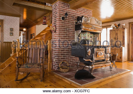 Old Legare's Rural antique wood stove in the living room a Canadiana cottage style fieldstone residential home built to look - Stock Photo