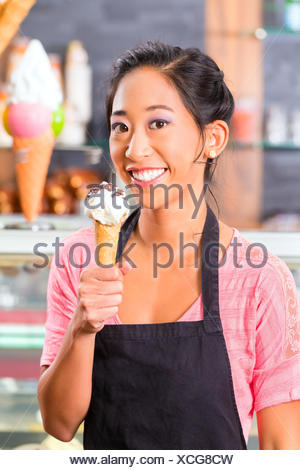 Young Asian saleswoman in an ice cream parlor with ice cream cornet - Stock Photo