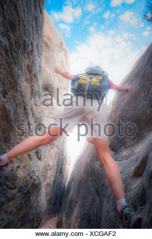 A female hiker as she stands above a trail through a narrow slot canyon in the Canyonlands National Park. - Stock Photo