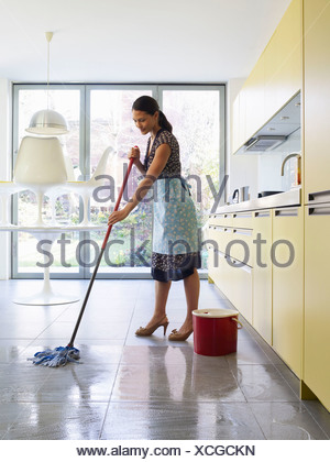 Young woman mopping kitchen floor - Stock Photo