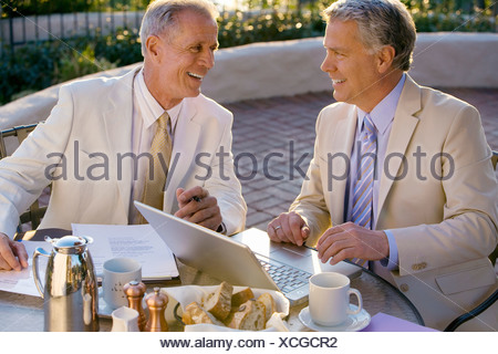 Two mature businessmen sitting at outdoor restaurant table, one man using laptop, smiling, side view - Stock Photo