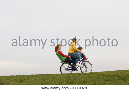 A young family riding on a bike together - Stock Photo