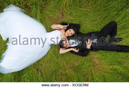 Bride and groom lying on grass - Stock Photo