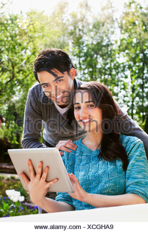 Portrait of young couple with digital tablet in garden - Stock Photo