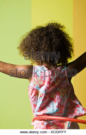 Little girl playing with plastic hoop, rear view - Stock Photo