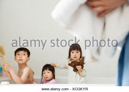 Brother and sisters in bath playing - Stock Photo