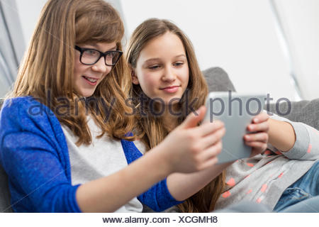 Sisters using digital tablet together at home - Stock Photo