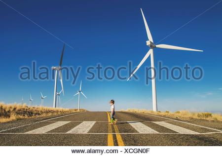 Young boy (2-3) walking across road with wind mills on background - Stock Photo