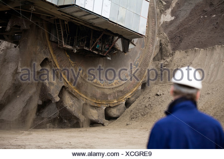 Worker standing by a bucket-wheel excavator, Grevenbroich, Germany - Stock Photo