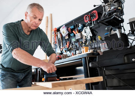 Man working with wood in home workshop - Stock Photo