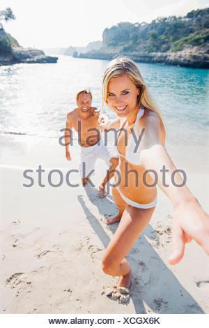 Spain, Majorca, woman pulling man's hand on beach - Stock Photo