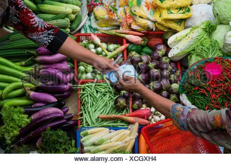 Cropped Image Of Customer Paying To Vendor In Market - Stock Photo