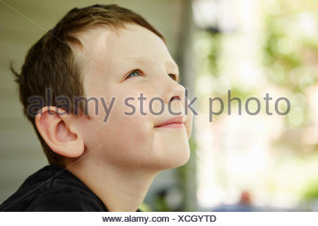 Close up profile portrait of boy in forest - Stock Photo