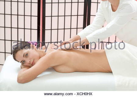 Young woman receiving massage, smiling - Stock Photo