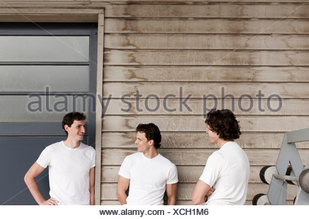Men standing and chatting on front porch - Stock Photo