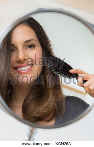 Young woman brushing hair in mirror - Stock Photo