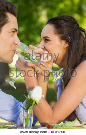 Couple drinking champagne at outdoor café - Stock Photo