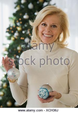 Senior woman holding Christmas ornaments - Stock Photo