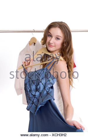 Portrait of a teenage girl holding up a dress on a hanger - Stock Photo