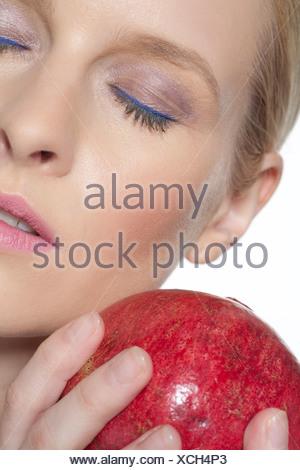 Female blonde hair off her face, wearing blue eyeliner, pearl pink eyeshadow, black mascara, peachy blusher and pink lipstick, - Stock Photo