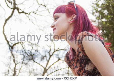 Portrait of smiling young woman with pink hair - Stock Photo