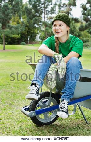 Full length of beautiful young environmentalist sitting in wheelbarrow at park - Stock Photo