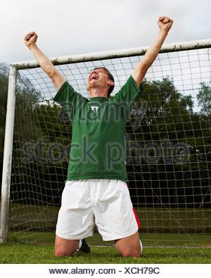Soccer player celebrating on field - Stock Photo
